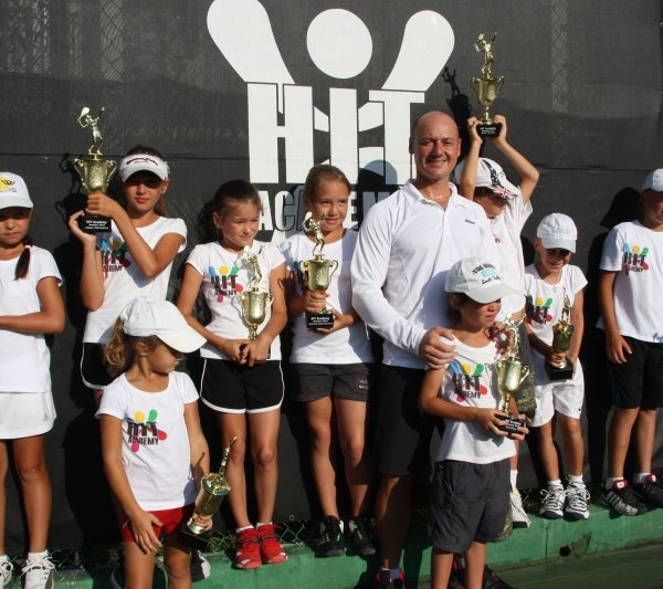 Tennis School player with trophies and coach